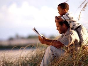 Pai e filho no campo lendo livro