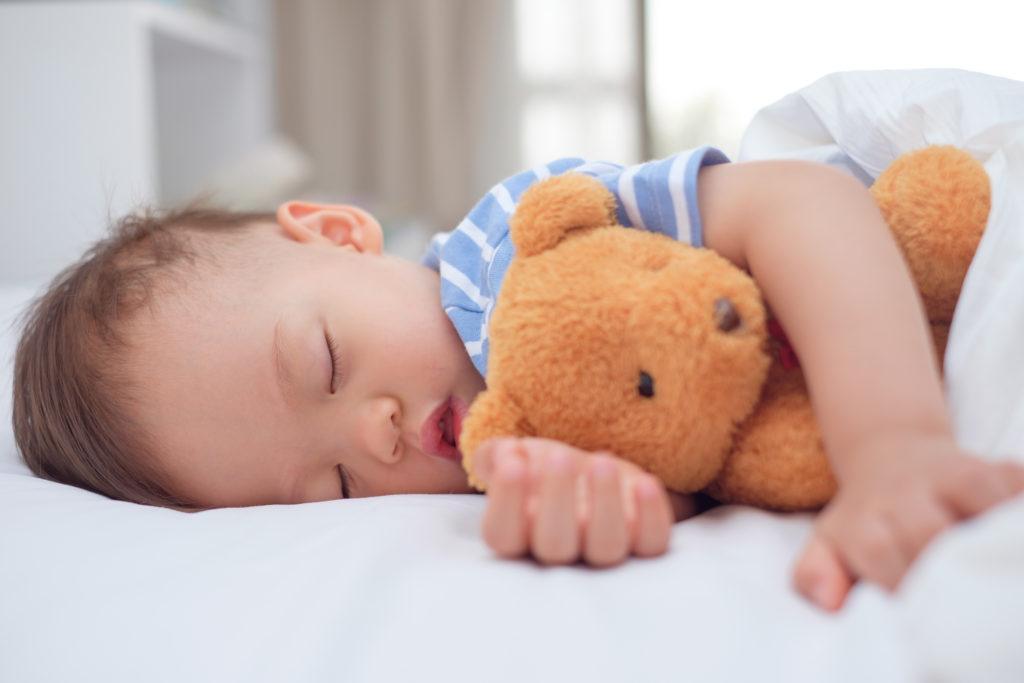 Criança dormindo com urso de pelúcia