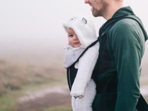 Pai caminha com seu filho preso ao peito